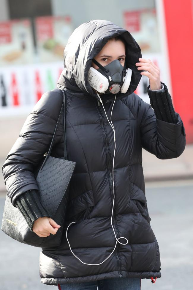 A woman wearing a face mask, the day after Prime Minister Boris Johnson put the UK in lockdown to help curb the spread of the coronavirus. Photo: Danny Lawson/PA Wire