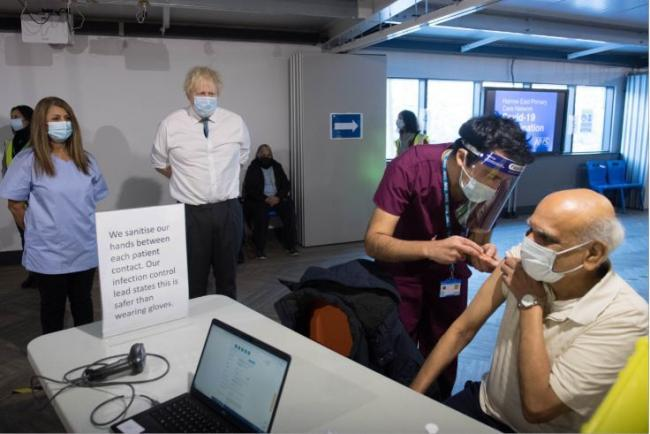 Prime Minister Boris Johnson watches on a as patient receives a jab at a vaccination centre at The Hive in north London. Credit: PA