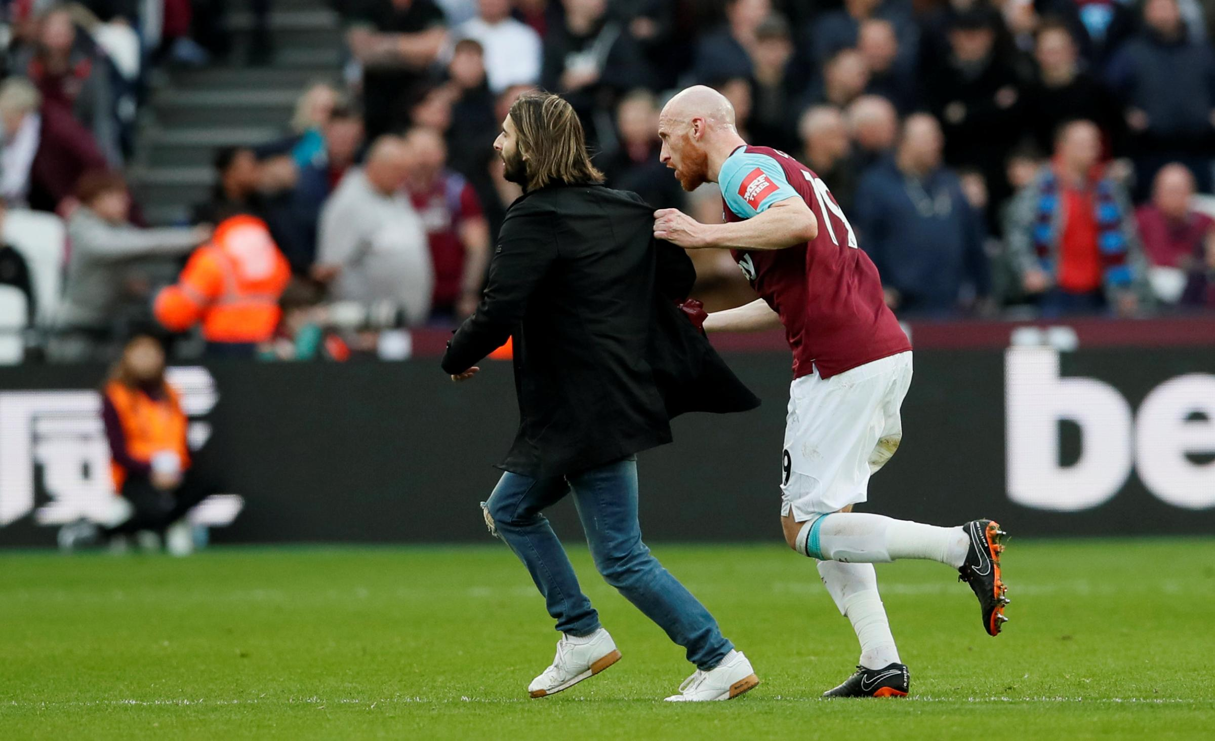 James Collins clashes with a pitch invader. Picture: Action Images