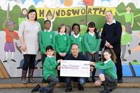 Nisa store owner Gaspar Munoz (centre) presents a cheque donation of £500 to Year 4 pupils and Friends of Handsworth representatives Sara Dudley-Hart and Andrew Golds