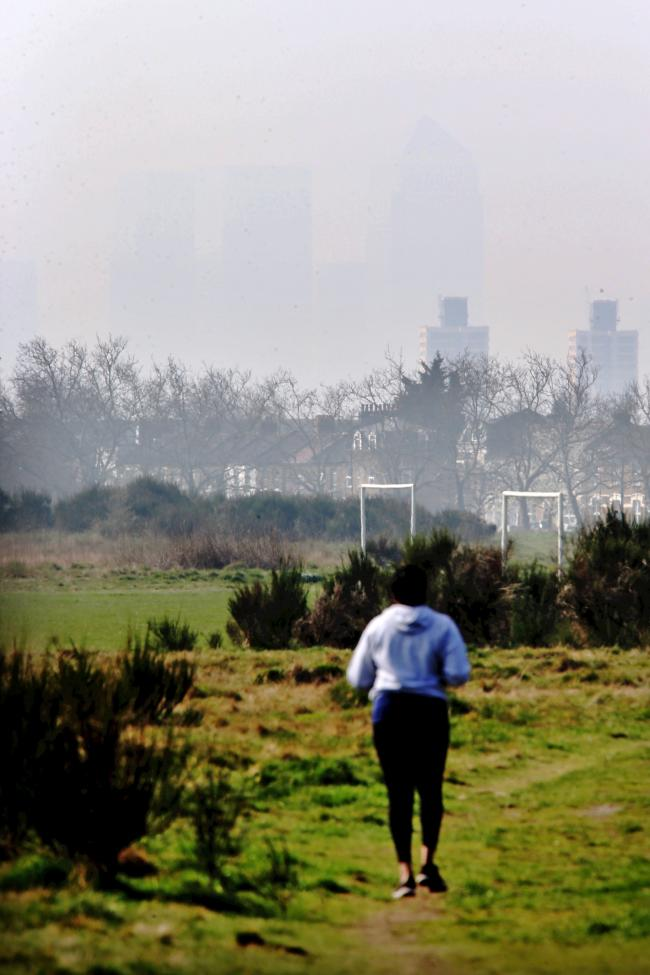 A runner on Wanstead Flats with towers at Canary Wharf just seen through pollution EL83439_2